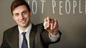Um homem de negócios em um terno realiza em sua mão um bitcoin de prata filme