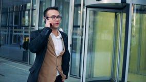 Um homem de negócios executivo, bem sucedido está fazendo um phonecall ao andar ao longo do centro do escritório Câmera épico ver filme