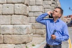 Um homem de negócios fala no telefone celular, e na outra mão veste vidros pretos, ao andar através de uma parte velha da cida imagens de stock