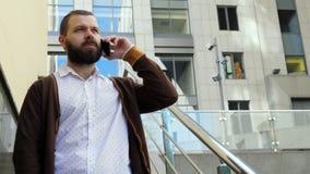 Um homem de negócios farpado do homem está estando nas escadas do centro de negócios e está falando pelo telefone O homem é satis filme