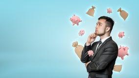 Um homem de negócios farpado novo profundamente no pensamento com mealheiros pequenos e os sacos do dinheiro que voam em torno de Foto de Stock