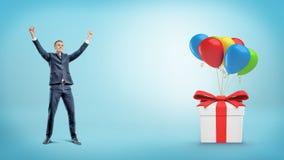 Um homem de negócios feliz com mãos levantou levantar-se atrás de uma caixa de presente amarrada a muitos balões imagem de stock