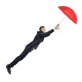 Um homem de negócios guarda a um guarda-chuva vermelho aberto que o mantenha ao mar no ar imagens de stock royalty free
