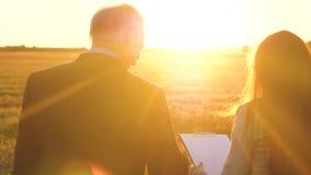 Um homem de negócios idoso no terno sério com dá o plano de trabalho à mulher de negócio nova da empresa na noite em brilhante filme