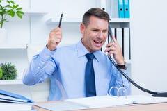 Um homem de negócios irritado que telefona em sua mesa Fotografia de Stock Royalty Free