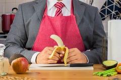 Um homem de negócios no avental vestindo do terno e do laço vermelho e em guardar uma banana descascada pequena na cozinha imagem de stock