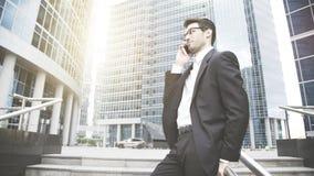 Um homem de negócios novo é de fala e de sorriso no telefone nas escadas Imagens de Stock