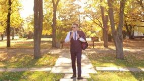 Um homem de negócios novo bem sucedido anda no parque do outono e come o gelado video estoque