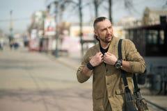 Um homem de negócios novo está andando com um saco na rua imagens de stock