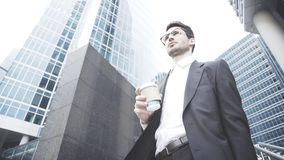 Um homem de negócios novo está guardando uma xícara de café na rua Imagens de Stock Royalty Free