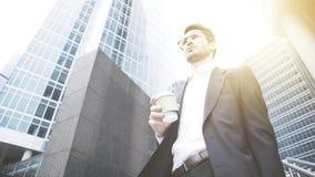 Um homem de negócios novo está guardando uma xícara de café na rua Foto de Stock