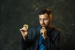 Um homem de negócios novo guarda uma moeda do bitcoite em sua mão fotografia de stock royalty free