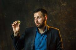Um homem de negócios novo guarda uma moeda do bitcoite em sua mão fotos de stock royalty free