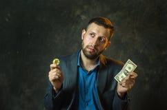 Um homem de negócios novo guarda uma moeda do bitcoite em sua mão imagens de stock royalty free