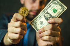 Um homem de negócios novo guarda uma moeda do bitcoite em sua mão foto de stock royalty free