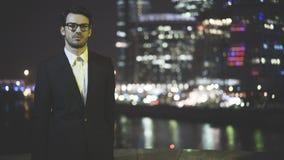 Um homem de negócios novo nos eyeglasess vestiu-se em um terno preto na noite Fotos de Stock Royalty Free