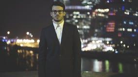 Um homem de negócios novo nos eyeglasess vestiu-se em um terno preto na noite Foto de Stock Royalty Free