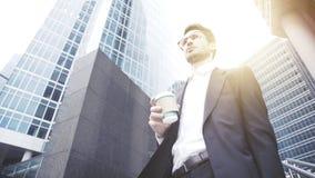 Um homem de negócios novo nos vidros que bebe o café em uma baixa Imagem de Stock Royalty Free