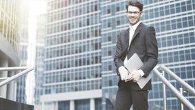 Um homem de negócios novo que está no riso ao ar livre Imagens de Stock