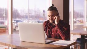 Um homem de negócios novo que fala no telefone e que trabalha em um portátil em um café vídeos de arquivo