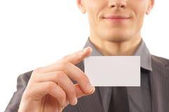 Um homem de negócios novo que prende um cartão Fotografia de Stock