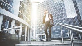 Um homem de negócios novo resolve uma pergunta no telefone nas escadas Fotos de Stock Royalty Free