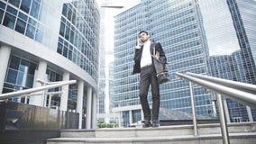 Um homem de negócios novo resolve uma pergunta no telefone nas escadas Imagens de Stock