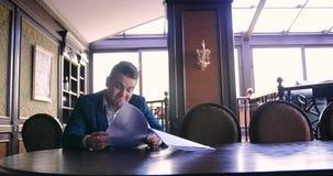 Um homem de negócios novo senta-se em um escritório chique e é descontentado com um contrato de papel, recusa assinar, irritado,  vídeos de arquivo