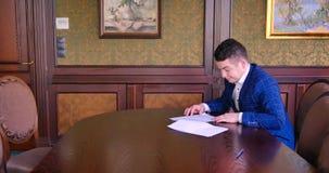 Um homem de negócios novo senta-se em um escritório chique e é insultado com um contrato de papel, recusa assinar, irritado, desf vídeos de arquivo
