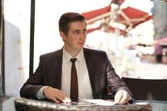Um homem de negócios novo veio almoçar em um café da rua, senta-se em uma tabela e olha-se o menu com alimento fotos de stock