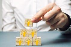 Um homem de negócios põe blocos de madeira com uma ampola de uma ideia ou de uma inspiração Geração de ideias inovativas do negóc imagens de stock royalty free