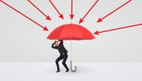 Um homem de negócios pequeno que esconde sob um grande guarda-chuva vermelho que o proteja das setas vermelhas imagens de stock