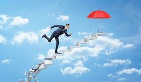 Um homem de negócios que corre acima em passos concretos de desintegração através das nuvens para alcançar um guarda-chuva vermel Fotos de Stock Royalty Free