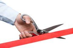 Um homem de negócios que corta uma fita vermelha do cetim Fotos de Stock Royalty Free