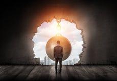 Um homem de negócios que está com girado para trás e que olha na cidade através de um furo da parede feito por uma bola de destru foto de stock