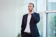 Um homem de negócios que fala em um telefone celular, homem de negócios que fala em t Fotos de Stock Royalty Free