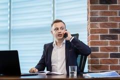 Um homem de negócios que fala em um telefone celular, homem de negócios que fala em t Foto de Stock