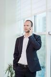 Um homem de negócios que fala em um telefone celular, homem de negócios que fala em t Foto de Stock Royalty Free