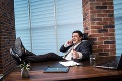 Um homem de negócios que fala em um telefone celular, homem de negócios que fala em t Imagem de Stock