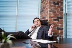 Um homem de negócios que fala em um telefone celular, homem de negócios que fala em t Fotografia de Stock