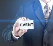 Um homem de negócios que guarda um sinal branco com o evento da mensagem Fotografia de Stock Royalty Free