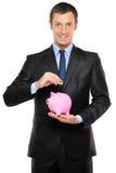 Um homem de negócios que põr uma moeda em um banco piggy Fotografia de Stock Royalty Free