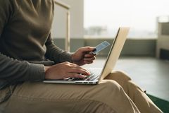 Um homem de negócios que senta-se com o portátil em seus joelhos e mão toma o cartão imagem de stock royalty free