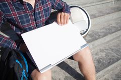Um homem de negócios que senta-se na rua abre seu portátil fotos de stock royalty free