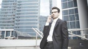 Um homem de negócios sério está falando no telefone nas escadas Foto de Stock