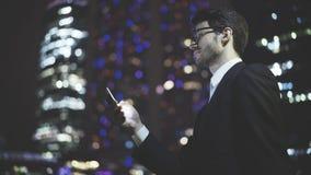 Um homem de negócios texting uma mensagem no telefone na noite Fotos de Stock Royalty Free