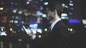 Um homem de negócios texting uma mensagem no telefone na noite Foto de Stock Royalty Free