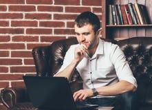 Um homem de negócios trabalha no portátil no escritório Senta-se na tabela no fundo de uma parede decorativa sob a forma dos tijo fotos de stock
