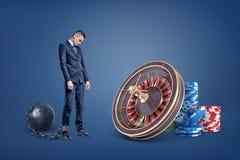 Um homem de negócios triste acorrentado a uma bola do ferro está perto de uma roleta do casino e das pilhas da microplaqueta imagem de stock