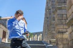 Um homem de negócios verifica algo em seu telefone celular, ao andar através de uma parte velha da cidade foto de stock royalty free
